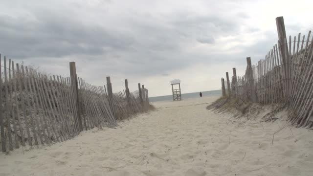 ビーチ小屋と海につながるパス - オオハマガヤ属点の映像素材/bロール