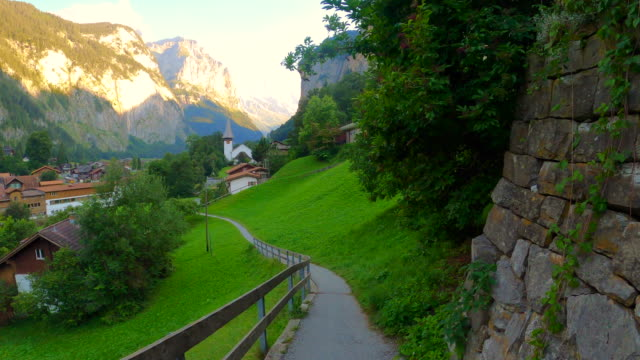 path leading from downtown lauterbrunnen to the church and staubbach falls on the right - falls church stock videos & royalty-free footage