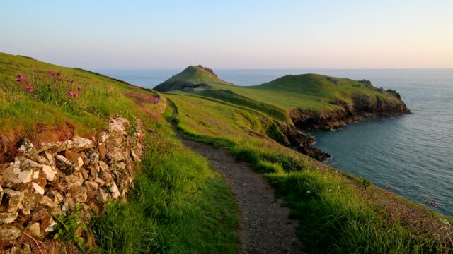 path on rocky shore at sunrise in spring, the rumps, wadebridge, cornwall, england, united kingdom, europe - cornwall england stock-videos und b-roll-filmmaterial