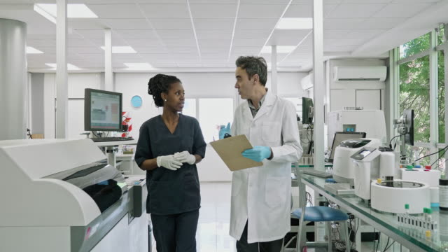 pathologist and technician having a conversation walking at lab - tecnico video stock e b–roll