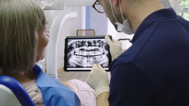 vídeos de stock, filmes e b-roll de paciente e dentista que discutem sobre o raio x médico - dentista
