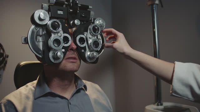 ms. patient answers questions as optometrist adjusts lenses on phoropter during routine eye exam. - lens optical instrument stock videos & royalty-free footage