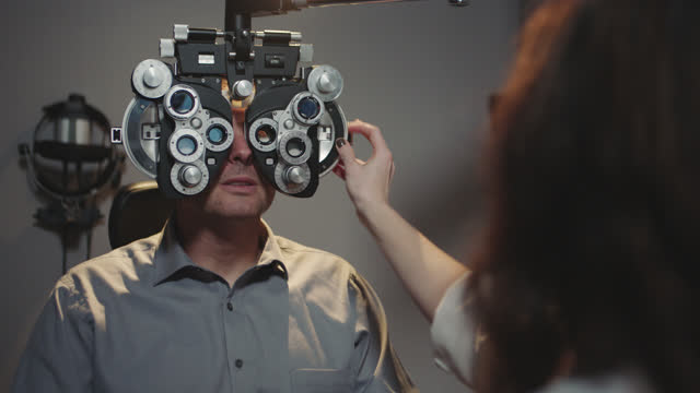 ms ots. patient answers questions as optometrist adjusts lenses on phoropter during routine eye exam. - 問う点の映像素材/bロール
