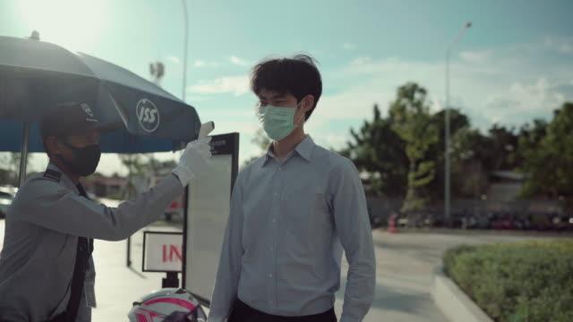 患者アジア人男性の顔と手温度計チェック温度 - 小児科医点の映像素材/bロール