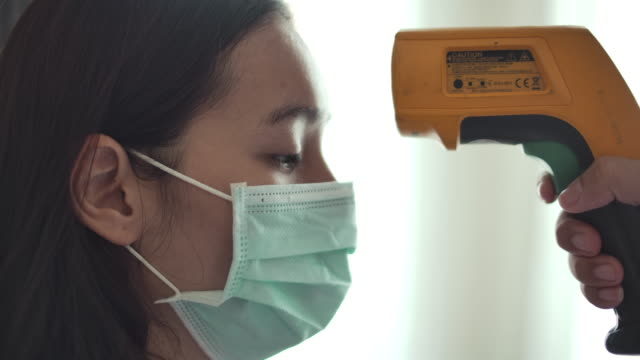 patient asian woman face and doctor hand with thermometer check temperature - thermometer stock videos & royalty-free footage