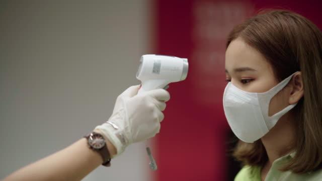 患者アジアの女性の顔と温度計チェック温度と手 - 温度計点の映像素材/bロール