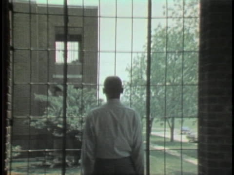 patient at a mental institution stares out a barred window. - schizophrenia stock videos & royalty-free footage