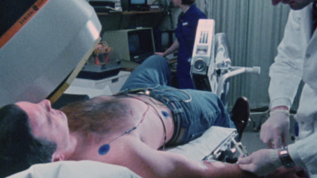 1983 MONTAGE Patient being injected with short half-life radioactive material and undergoing medical stress test under a doctor's supervision / United Kingdom
