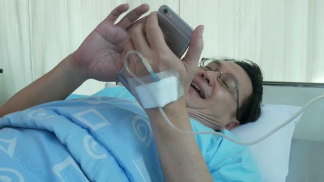 vidéos et rushes de homme d'affaires patient allongé sur le lit, avec téléphone, rire - rétablissement