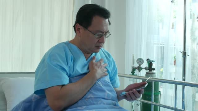 vídeos de stock, filmes e b-roll de empresário de paciente sente-se na cama, usando telefone, ataque cardíaco - heart attack