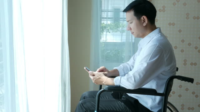 patient businessman sit on wheelchair , using phone - despair stock videos & royalty-free footage