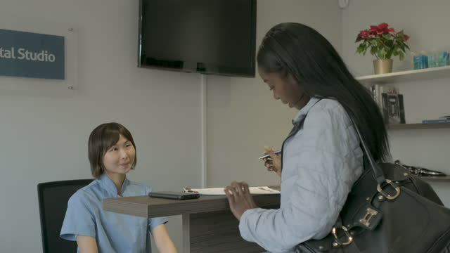 patient filling out questionnaire at front desk - clinic stock videos & royalty-free footage