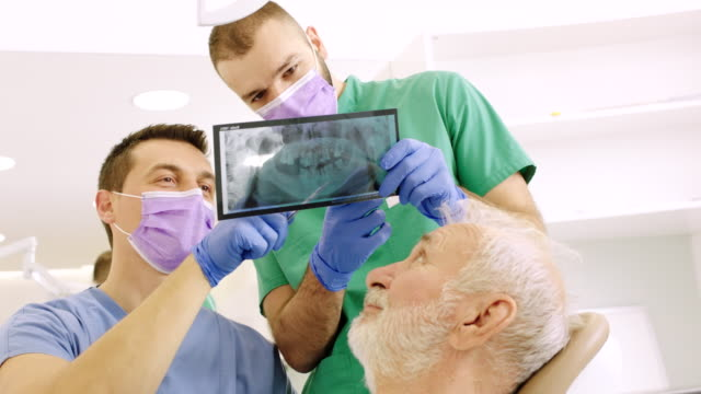 vídeos de stock e filmes b-roll de patient getting a dental treatment at clinic - higiene dental