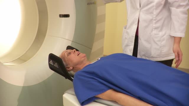 vídeos de stock, filmes e b-roll de ms pan patient going into cat scanner operated by technician / burlington, vermont, usa - máquina de tomografia axial computadorizada