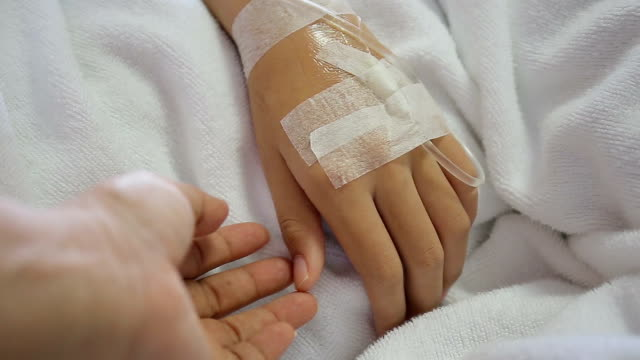 Patient hand in bed with one hand being hold to be supportive in hospital encourage