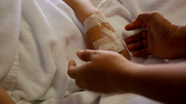 patient hand in bed with one hand being hold to be supportive in hospital encourage - iv drip stock videos and b-roll footage