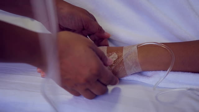 patient hand in bed with one hand being hold to be supportive in hospital encourage - saline stock videos and b-roll footage