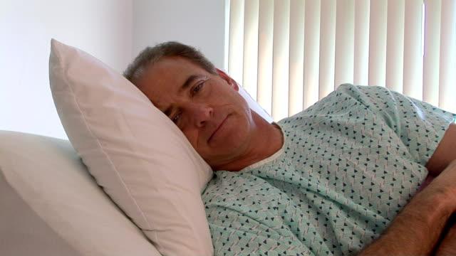 patient in hospital room - endast en medelålders man bildbanksvideor och videomaterial från bakom kulisserna