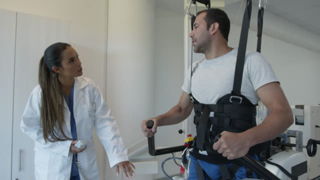 patient in physical therapy doing exercises with an exoskeleton robot on treadmill guided by a physiotherapist - limb body part stock videos & royalty-free footage