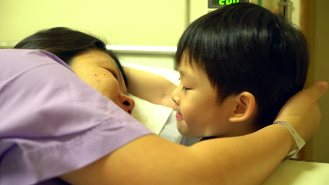 patient laying on bed for check pulse or touch from her son , take care concept.son kiss her mother as patient lying on the bad. - female reproductive system stock videos & royalty-free footage