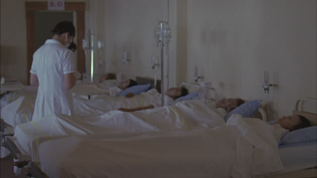 stockvideo's en b-roll-footage met a patient lays in a hospital bed while a nurse tends to him. - ziekenzaal