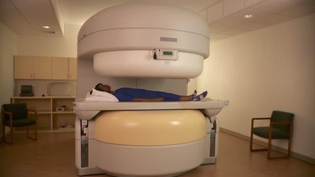 vídeos y material grabado en eventos de stock de ws zi patient lying down into mri scanner in hospital room / burlington, vermont, usa - equipo médico de escaneo