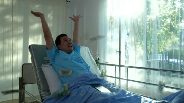vídeos de stock e filmes b-roll de patient man day dreaming for cash money falling on bed - paralisia