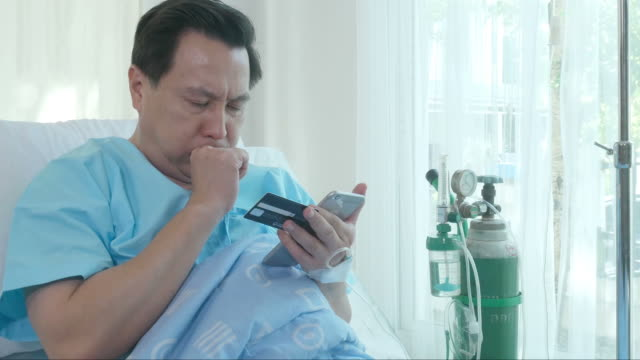 vídeos de stock e filmes b-roll de patient man sit on bed , using phone and credit card ,coughing - paralisia