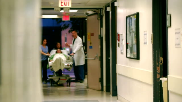 patient on gurney through doors - casualty stock videos & royalty-free footage