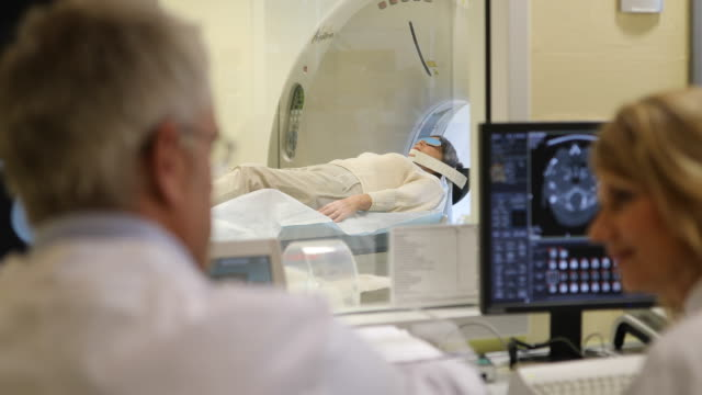 Patient on MRI scanner with doctors in hospital