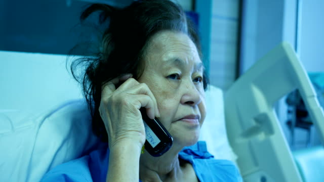 patient senior woman sitting on bed , using phone - over 80 stock videos and b-roll footage