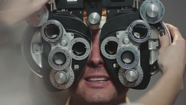 cu ots. patient smiles as optometrist lifts and adjusts phoropter over his eyes. - optical instrument stock videos & royalty-free footage