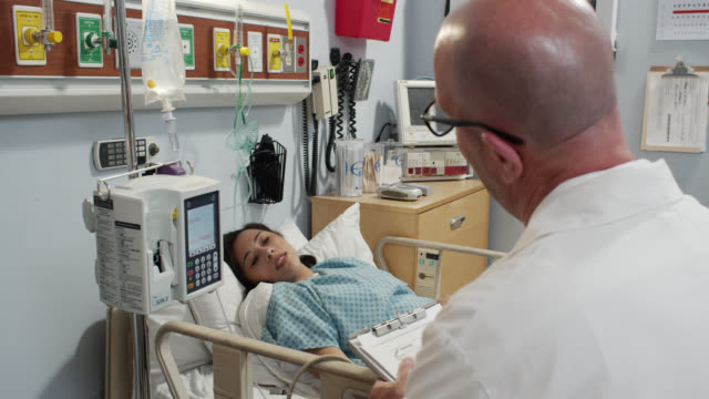 patient speaking to doctor from hospital bed - iv drip stock videos & royalty-free footage