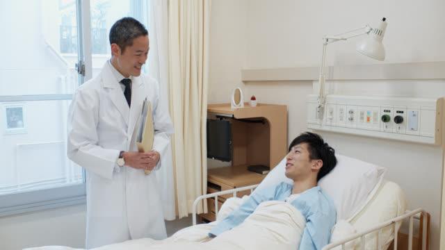 病院のベッドから医者に話している患者 - 病棟点の映像素材/bロール