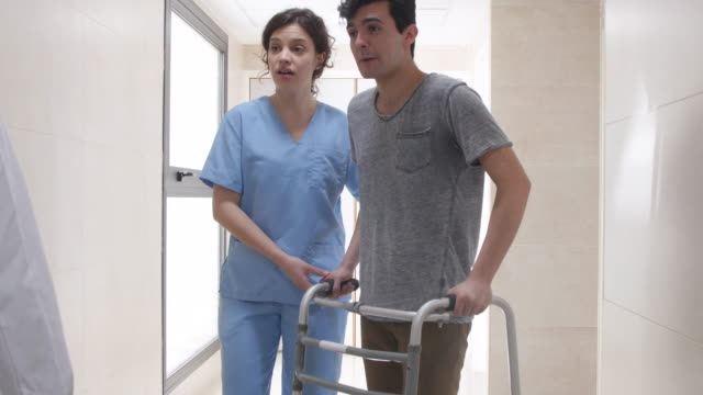 patient using a walker while nurse is walking next to him and then friendly doctor greeting him very friendly - recovery stock videos and b-roll footage