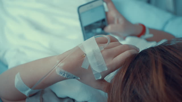 patient using smart phones while saline solution,slow motion - blanket background stock videos & royalty-free footage