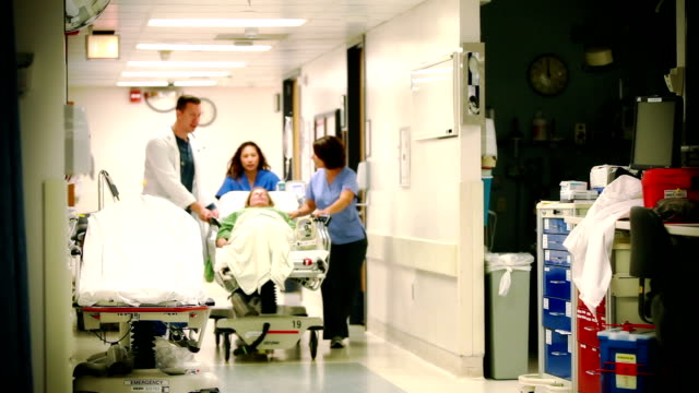 patient wheeled by on gurney - casualty stock videos & royalty-free footage