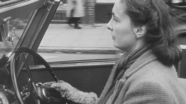 vídeos de stock e filmes b-roll de 1949 montage patient with polio paralysis driving through city streets in car fitted with handicap controls / united kingdom - pólio