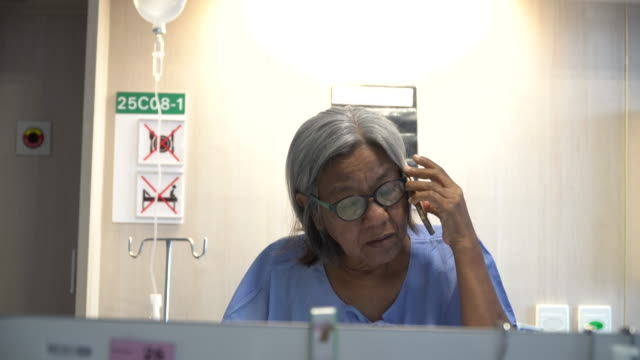 Patient woman talking on phone in hospital bed