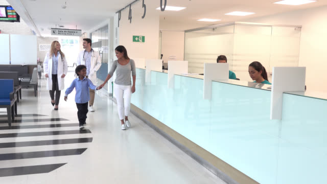 Patients and doctors walking through the corridor of a hospital