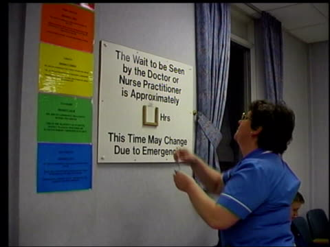 lib int hospital patients at reception area of outpatients' department nurse changing waiting time to two and a half hours patients in waiting area... - outpatient care stock videos & royalty-free footage