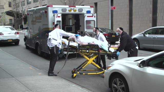 patients being unloaded from an ambulance and brought into a hospital during the coronavirus outbreak in new york city - new york city stock videos & royalty-free footage