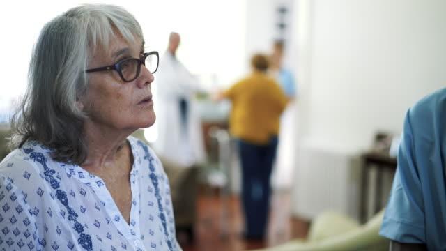stockvideo's en b-roll-footage met patiënten in het verpleeghuis praten met zwarte mannelijke verpleegkundige - woongemeenschap ouderen