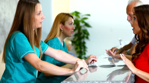 patients making medical appointments. - receptionist stock videos & royalty-free footage