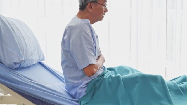 患者の先輩アジア人男性は病院のベッドで激しい痛みを感じた。 - 病気点の映像素材/bロール