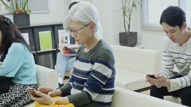 病院の待待室に座っている患者 - 待つ点の映像素材/bロール