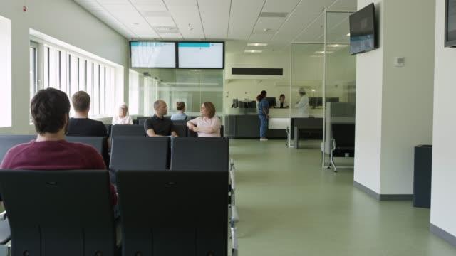 vidéos et rushes de patients assis dans la salle d'attente à l'hôpital - salle d'attente