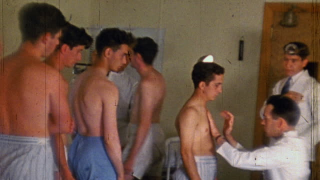 Patients standing in line one by one receiving cursory physical examination by doctors at National Youth Administration camp during WWII / United...