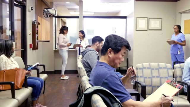 patients wait in a busy emergency room waiting area - clinica medica video stock e b–roll