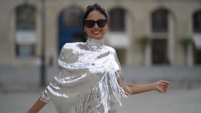 stockvideo's en b-roll-footage met patricia gloria contreras wears quay sunglasses, earrings, a silver sequined shiny fringed turtleneck top from balmain, levi's white ripped denim... - zoom out